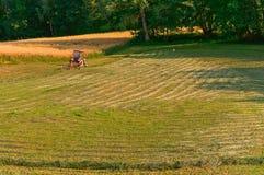 Im Abstand ein Traktor, der auf einem Gebiet, Ackerland, landwirtschaftliche Felder arbeitet Stockfotografie