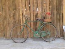 Im altem Stil rostiges grünes Fahrrad und hölzerne Wand Stockbild
