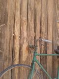 Im altem Stil rostiges grünes Fahrrad und hölzerne Wand Stockfotos