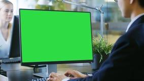 Im Büro arbeitet der Geschäftsmann an seinem Schreibtisch auf einem persönlichen Comput stockbilder