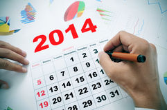 Im Büro mit einem Kalender 2014 Stockfotografie