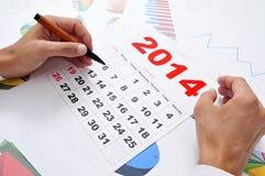 Im Büro mit einem Kalender 2014 Stockfotos