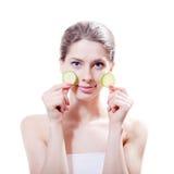 Im Badekurort: attraktives Mädchen der jungen Schönheit, das mit Scheiben der Gurke in den Händen steht u. Kamera auf Weiß betrac Stockfoto