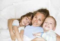 Im Bett mit den Kindern morgens aufwachen Stockfoto
