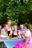 Im Biergarten - Freunde auf einer Tabelle mit Bier Lizenzfreie Stockfotografie