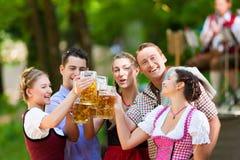 Im Biergarten - Freunde vor Band Stockfotografie
