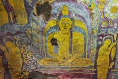 Im Dambulla-Höhlentempel Altes schäbiges Bild von einem Buddha auf Stockfotografie