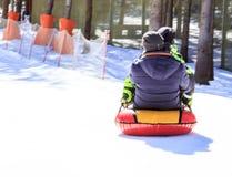Im Dezember 2009 Mädchen, das auf einem Schneehügel rodelt Stockfotografie
