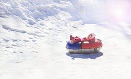 Im Dezember 2009 Mädchen, das auf einem Schneehügel rodelt Stockbild