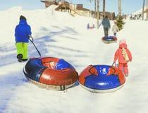 Im Dezember 2009 Mädchen, das auf einem Schneehügel rodelt Lizenzfreies Stockbild