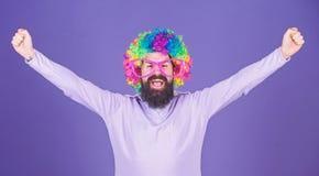 Im en vinnare Sk?ggig man som firar seger i clownperukfrisyr Man i modeperuk med lycklig segra gest arkivbilder