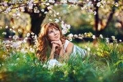 Im Frühjahr liegt eine junge rothaarige Frau in einem weißen Sommerkleid auf dem Gras, schaut weg und träumt in einem blühenden G Stockbilder