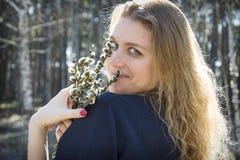 Im Frühjahr im Waldmädchen mit einem Blumenstrauß der Weide Sie genießt den Geruch lizenzfreies stockbild