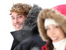 Im Freienpaare, die im Winterschnee lächeln Lizenzfreie Stockfotografie