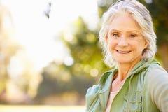Im Freienportrait der lächelnden älteren Frau Stockfoto