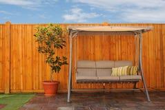 Im Freienschwingen-Stuhl vor hölzernem Zeder-Zaun Stockbilder
