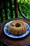 Im Garten auf einem alten Weinleseholzstuhl ein Teller mit einem Mohnblumenkuchen lizenzfreies stockbild