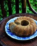 Im Garten auf einem alten Weinleseholzstuhl ein Teller mit einem Mohnblumenkuchen lizenzfreie stockbilder