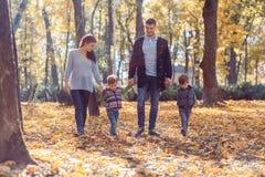 Im?genes naturales de una familia de cuatro miembros feliz que tiene outsiade de la diversi?n en un d?a soleado del oto?o Concept fotos de archivo