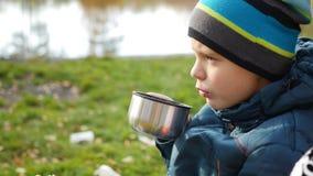 Im Herbstparkkerl, der auf dem heißen Tee des Rasens und des Getränks, Weg in der Frischluft sitzt nahaufnahme Stockfoto
