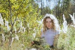 Im Herbstwald auf einem gelockten Mädchen der Lichtung im hohen Gras in Stockfoto