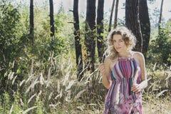 Im Herbstwald auf einem gelockten Mädchen der Lichtung im hohen Gras in Stockfotografie