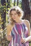 Im Herbstwald auf einem gelockten Mädchen der Lichtung im hohen Gras in Stockbilder