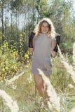Im Herbstwald auf einem gelockten Mädchen der Lichtung im hohen Gras in Lizenzfreie Stockfotos