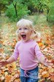 Im Herbstwald kleine blonde schreit das Mädchen enthusiastisch Lizenzfreie Stockfotos