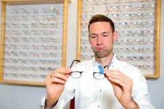 Im jungen Mann des Optikergeschäftes mit defekten Gläsern Stockfoto