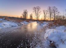 Im kalten Morgen der gefrorene kleine Fluss auf Sonnenaufgang Stockbild