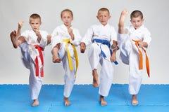 Im karategi schlugen vier Athleten Tritt mae-geri stockfoto