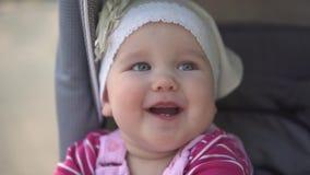 Im Kinderwagen sitzendes und lächelndes Baby, slowmotion Schuss stock video