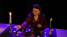 Im magischen Salon beleuchtet der Zigeuner Kerzen auf einer schwarzen Tabelle stock video