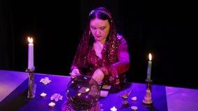 Im magischen Salon breitet der Zigeuner die Karten auf der schwarzen Tabelle im grellen Glanz aus stock video footage