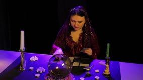 Im magischen Salon durch Kerzenlicht, wundert sich ein Zigeuner auf den Karten stock video