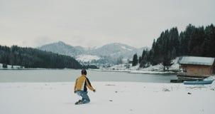 Im mittleren schneebedeckten See und im Berg mit dem großen Wald glücklich und dem freudig erregt Touristen, der auf dem Schnee d stock footage