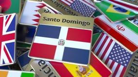 Im?n del recuerdo o insignia con el texto de Santo Domingo y bandera nacional entre los diversos El viajar al dominicano stock de ilustración