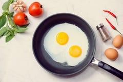 Im Prozess essen, Spiegeleier in einer Bratpfanne zum Frühstück lizenzfreie stockbilder