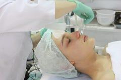 Im Sch?nheitssalon tut eine junge Frau eine Schale auf ihrem Gesicht lizenzfreies stockbild