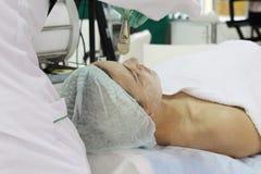 Im Sch?nheitssalon tut eine junge Frau eine Schale auf ihrem Gesicht lizenzfreie stockbilder