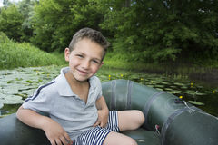 Im Sommer auf dem Fluss ein kleiner Junge, der in einem Gummiboot sitzt Stockfoto