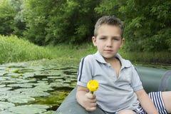 Im Sommer auf dem Fluss ein kleiner Junge, der in einem Gummiboot sitzt Stockbild