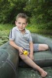 Im Sommer auf dem Fluss ein kleiner Junge, der in einem Gummiboot sitzt Lizenzfreies Stockbild
