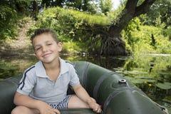 Im Sommer auf dem Fluss ein kleiner Junge, der in einem Gummiboot sitzt Stockbilder