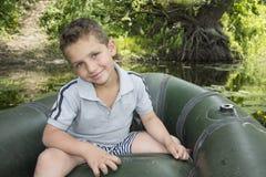 Im Sommer auf dem Fluss ein kleiner Junge, der in einem Gummiboot sitzt Lizenzfreie Stockbilder