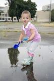 Im Sommer das Stadion, das ein kleines Mädchen mit einer Schaufel nahe Th spielt Stockbilder