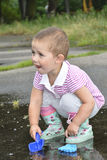 Im Sommer das Stadion, das ein kleines Mädchen mit einer Schaufel nahe Th spielt Stockfotos