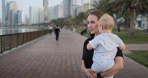 Im Sommer eine junge Mutter, die mit einem Kind entlang der Promenade geht stock video footage