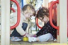 Im Sommer sind zwei kleine Mädchen glücklich, dass Freundinnen an spielen Lizenzfreies Stockfoto